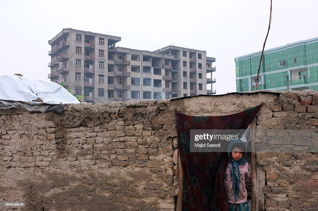 KABUL, AFGHANISTAN - FEBRUARY 03An internally displaced Afghan child peers out of a doorway as she waits to receive donations at Chamand babrak Camp, on February 3, 2013 in Kabul, Afghanistan. According to the UN refugee agency, Afghanistan's internally displaced population has reached half a million, although the actual figure is believed to be much higher.