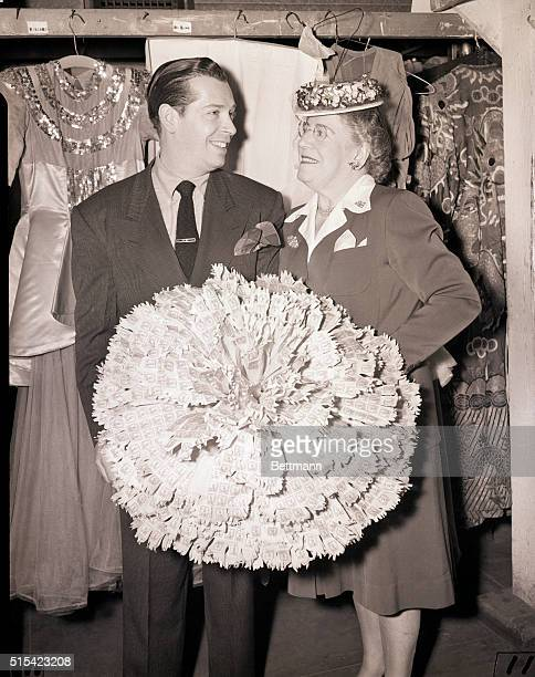 New York City Mrs Sandra Berle is discovering that 3750 ten cent war stamps make quite a large carnation as she accepts the mothers Day posey from...