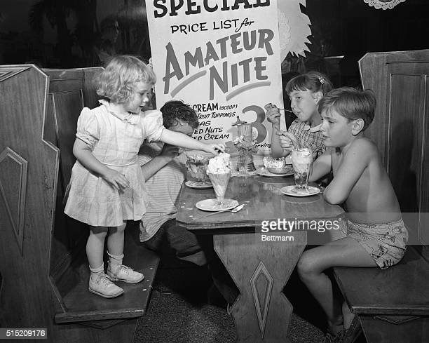 Hollywood CA ORIGINAL CAPTION READS Three youthful amatures watch Kristian Helmer 3 reach for the cherry atop her sundae Left to right Kristian...