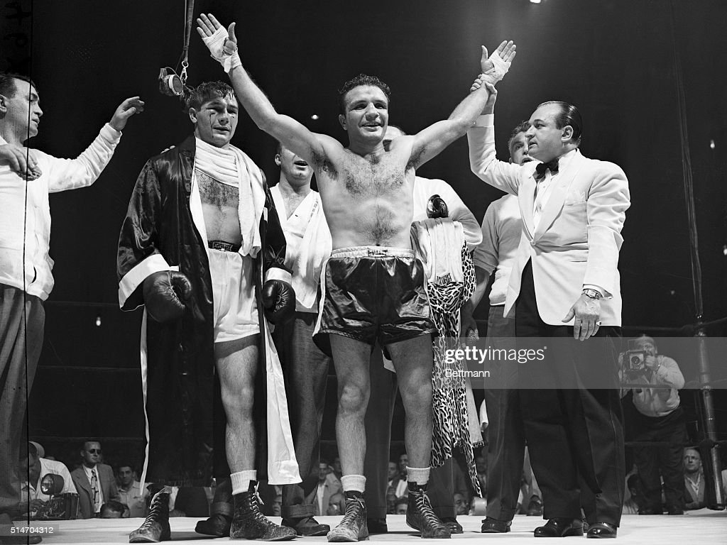 Unmarked and smiling, Jake LaMotta, the middleweight champion, raises his hands in victory after winning the decision over Tiberio Mitri in a 15 round title bout at Madison Square Garden, July 12th. Mitri (left), his face bloody and both eyes puffed, manages to scrape up a smile for the victor. Announcer Johnny Addie is at right.