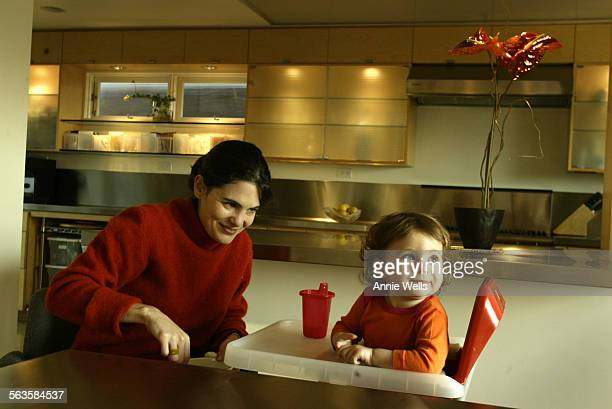 HM0108dayhouse Nina Hachigian give her daughter Sosi Day a snack in the dining room The dining table is an old lanuage lab desk that has been topped...