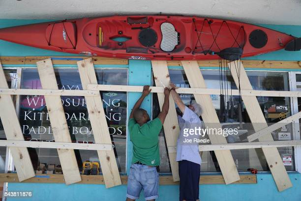 Jim DeSilva and Milton Ibanez put window protection on their business Sandy Point as they prepare for Hurricane Irma on September 7 2017 in Miami...