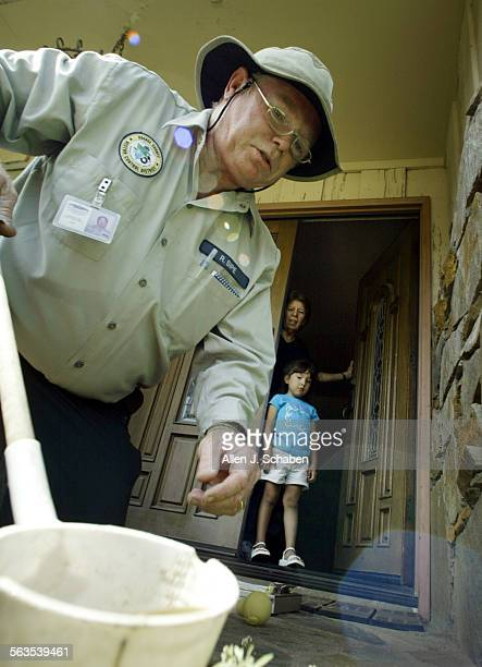 ME0917vectorAJS––Orange County vector control technician Russell Sipe collects a water sample at the home of Elveria Nicasio as Nicasio and her...