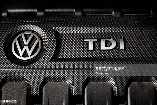 A VW and a TDI logo sit on the tubocharged direct injection diesel engine of a Volkswagen AG Passat TDI automobile in London UK on Wednesday Dec 2...