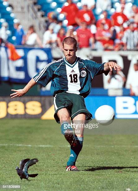 Sportler Fussball Dim Trikot der deutschenNationalmannschaft in Aktion mit Ball