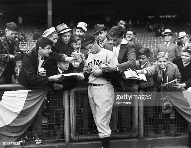 Joe Di Maggio new batting hero of the New York Yankees good naturedly signs autographs for young ball fans before the start of the third World Series...
