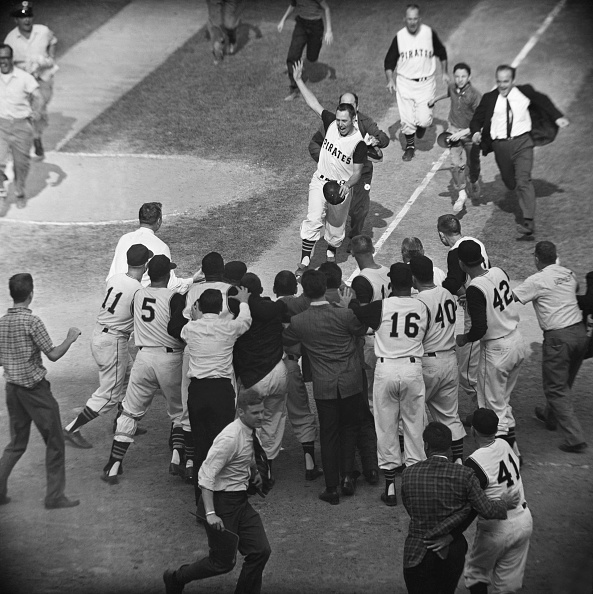 Pittsburgh PA Pirate Bill Mazeroski chased by a fan gets ready to cross home plate and is greeted by fans and fellow players after his ninth inning...