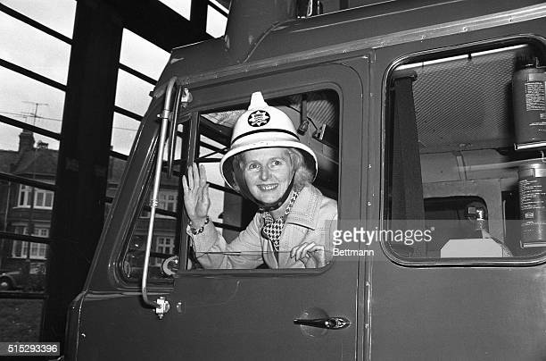 London England Conservative Party leader Margaret Thatcher tries on a fireman's helmet as she sits in the cab of a firetruck during a visit to...