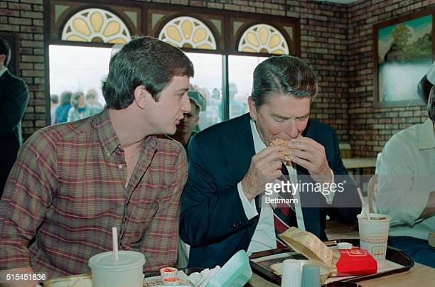 Tuscaloosa ALPresident Ronald Reagan takes a bite of a Big Mac as Charles Patterson chats with him during a brief campaign stop
