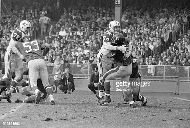 New York NY Dallas defensive end Bob Lilly wraps a bearhug around Giant quarterback YA Tittle despite Jack Stroud's blocking efforts in the second...