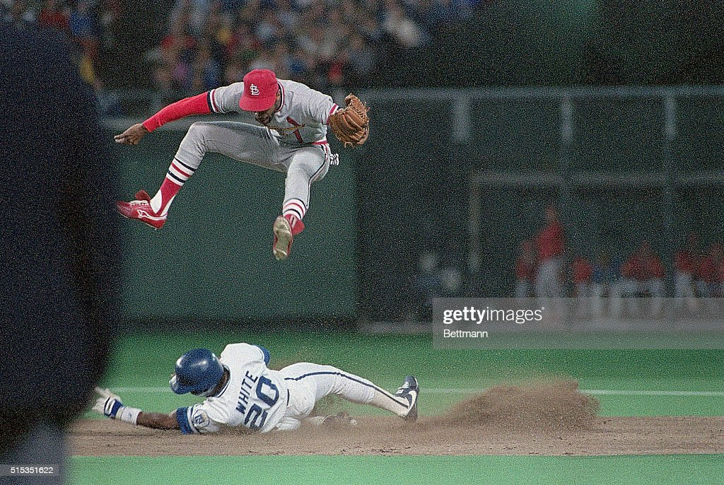 Kansas CityKansasCards' SS Ozzie Smith leaps for wild throw as Royals' Frank White steals second in second inning
