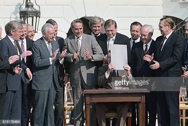Washington DC After signing the 1986 Tax Reform Bill President Reagan is shown seated with officials behind him Looking on behind the President from...