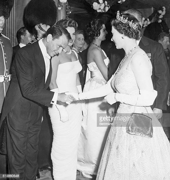 London England Entertainer Frank Sinatra bows as he is presented to smiling Queen Elizabeth at movie premiere here Oct 27 The film being shown was...