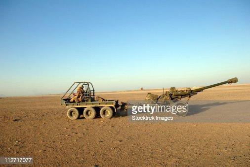 A 105mm light gun being towed by an all-terrain vehicle.