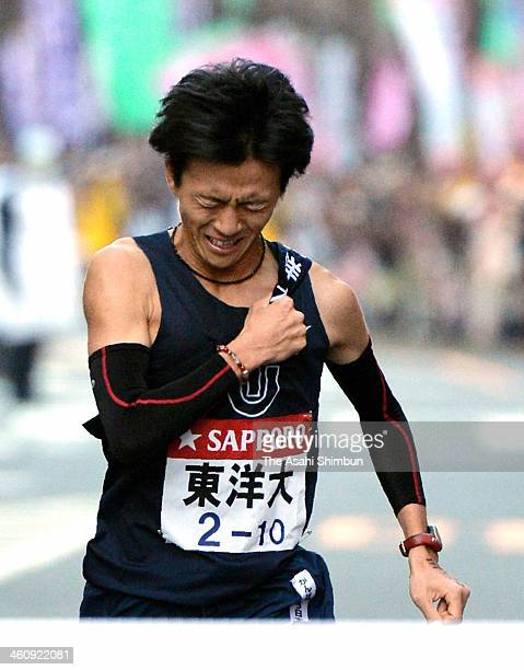 10th and final runner of the Toyo University Kento Otsu crosses the finishing line to win the 90th Hakone Ekiden on January 3 2014 in Tokyo Japan