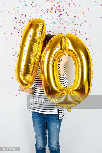 10th anniversary celebration party girl with golden balloons : Stock Photo