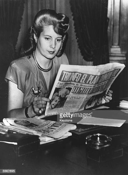 Eva Peron wife of Argentinian dictator Juan Peron reads a copy of 'Democrazia' the newspaper she owns