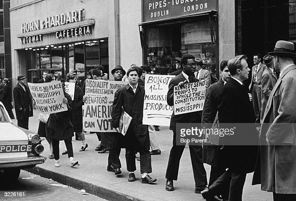 People marching with placards during an antisegregation demonstration on a sidewalk in front of Horn and Hardart Automat Cafeteria New York City