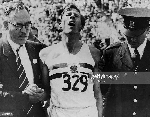 English athletics team manager George Truelove and a police officer help record holder Roger Bannister after what was dubbed 'The Mile Of The...