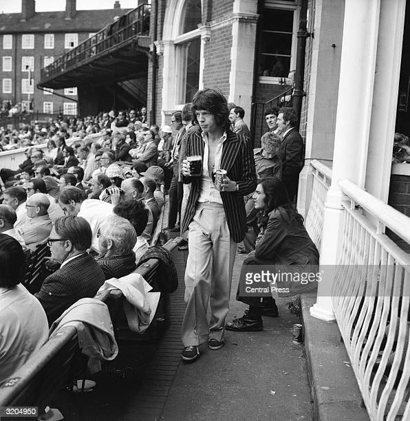 Mick Jagger returning to his seat at the Oval where he is watching the Cricket Test match between England and Australia with his wife Bianca