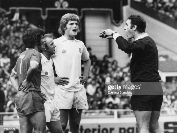 Gordon McQueen of Leeds United FC watches as referee R Matthenson sends off Kevin Keegan from Liverpool FC and Billy Bremner of Leeds United FC for...