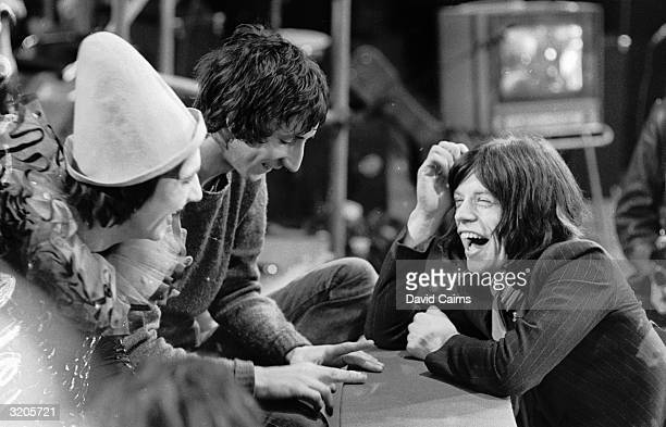 Mick Jagger the lead singer of the Rolling Stones chatting with the drummer of the Who Keith Moon and the band's chief songwriter and guitarist Pete...