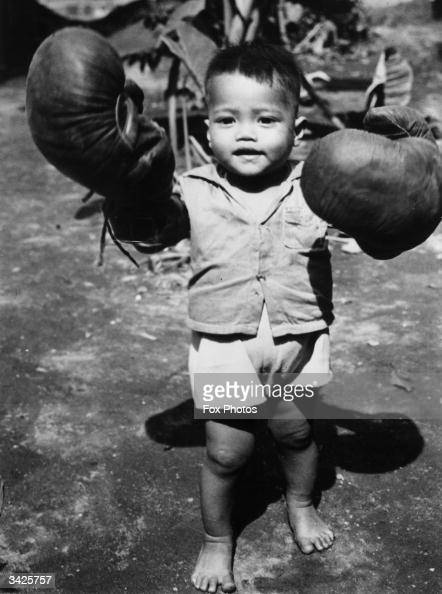 A young boy on Leyte Island in the Philippines with a pair of boxing gloves that an American soldier had given him