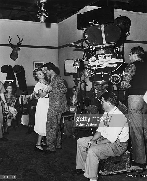 American actors Montgomery Clift and Shelley Winters dance while American director George Stevens watches on the set of his film 'A Place in the Sun'...