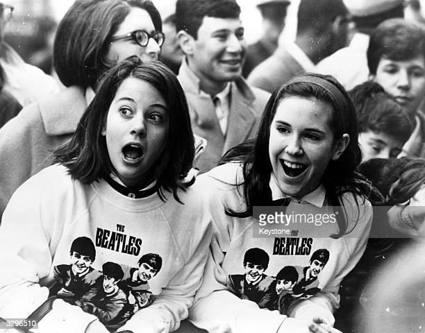 Two excited girls in Beatles sweatshirts amongst a crowd of fans in New York welcoming the group as they arrive at the airport
