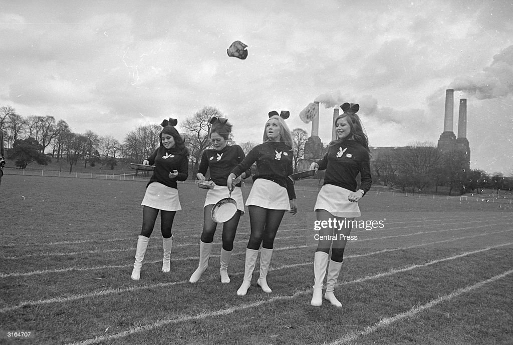 Playboy bunnies, (from left) Adria Aung, Myra Van Heck, Carmel Stratton and Dina Turner during a charity pancake race in Battersea Park, London. Battersea power station is in the background.
