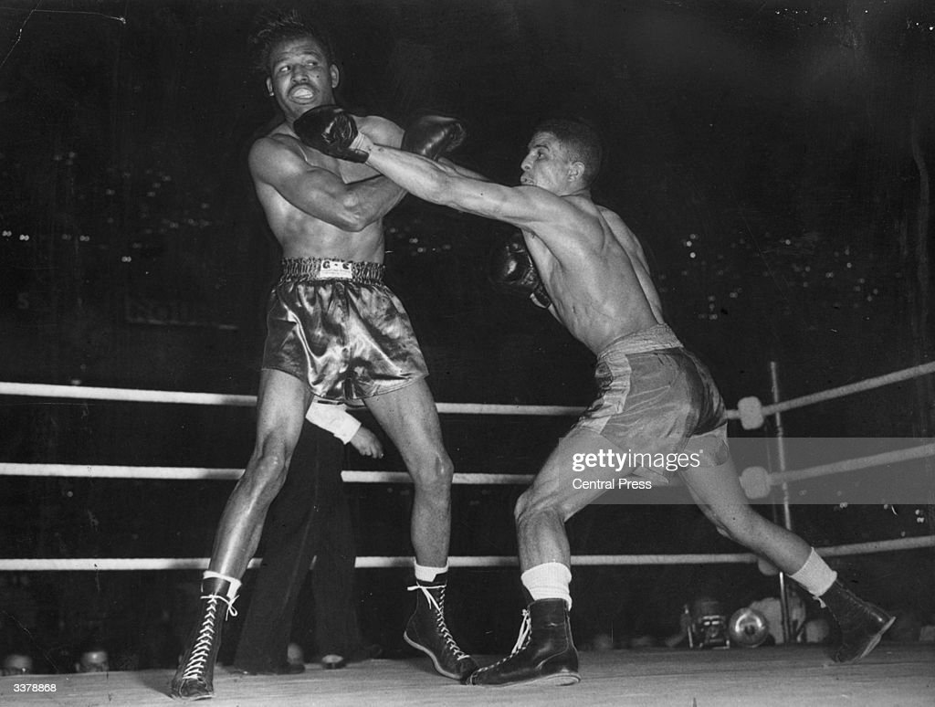 British boxer Randolph Turpin lands a straight left to Sugar Ray Robinson's chin on his way to beating the American for the world middleweight title...