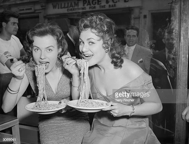Mirv Arvinen and Soho's Fair Queen Andria Loran try their hand at scoffing a plate of pasta at the Soho Fair spaghettieating contest on Frith Street...