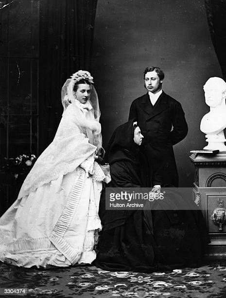 Prince Edward and his bride Princess Alexandra of Denmark just after their marriage posing with Queen Victoria