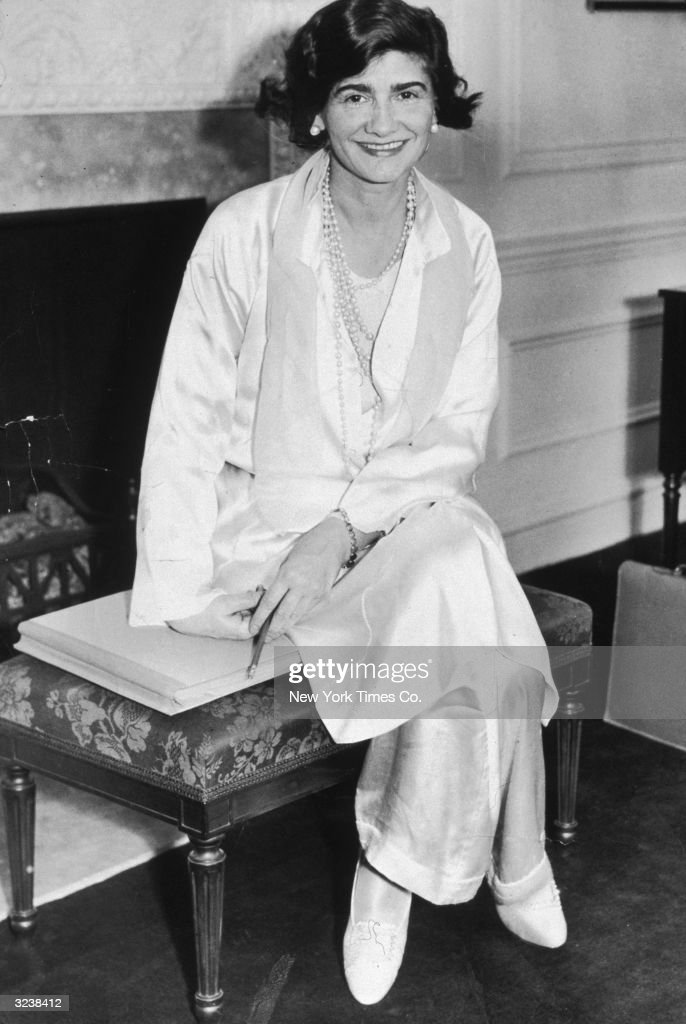 Portrait of French fashion designer Gabrielle 'Coco' Chanel (1883 - 1971) posing in her suite at the Hotel Pierre during her first visit to New York City. She wears a white silk jacket and pants with pearls.