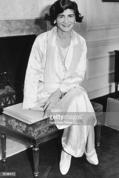 Portrait of French fashion designer Gabrielle 'Coco' Chanel posing in her suite at the Hotel Pierre during her first visit to New York City She wears...