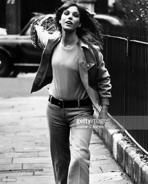 Model and actress Jane Birkin swings a basket along a London street