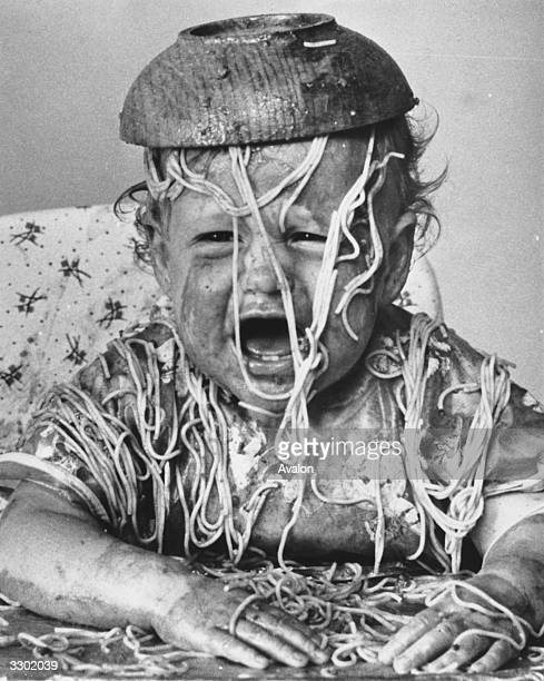 A young child crying with a bowl of spaghetti tipped over its head