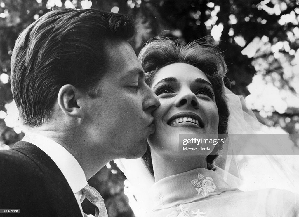 British costume designer Tony Walton kisses the cheek of his new bride, British actor and singer Julie Andrews, England. She wears her bridal veil.