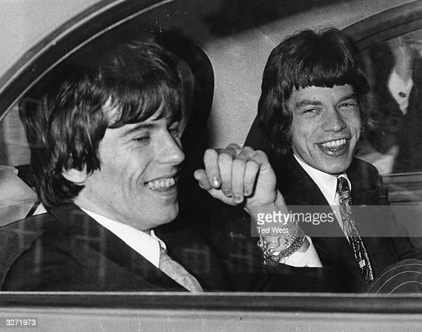 Rolling Stones songwriters guitarist Keith Richards left and singer Mick Jagger share a joke in the back of a car as they leave Chichester...