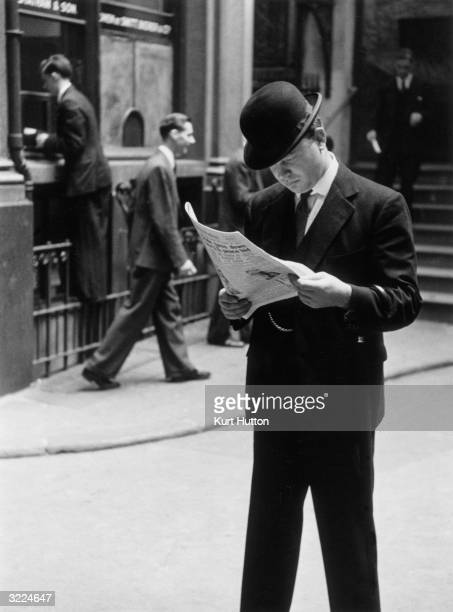 A businessman in a bowler hat peruses the financial column of a newspaper whilst crossing the road Behind him is a runner who passes prices to a...