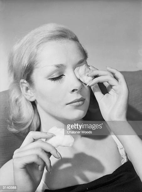 A model applies pads of cotton wool soaked in lotion to the eyes