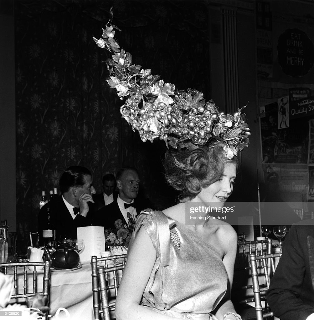 Lady Anne Tennant sports an unusual hat made of fake grapes at a society function.