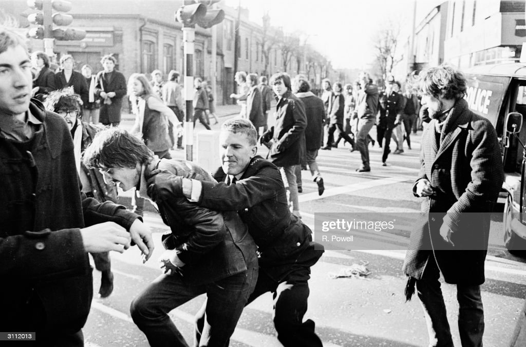An antiapartheid demonstrator being collared by a policeman outside the ground where Midland Counties are playing the Springboks