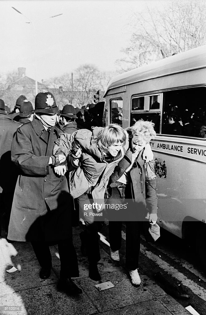 An antiapartheid demonstrator is helped to an ambulance by a policeman
