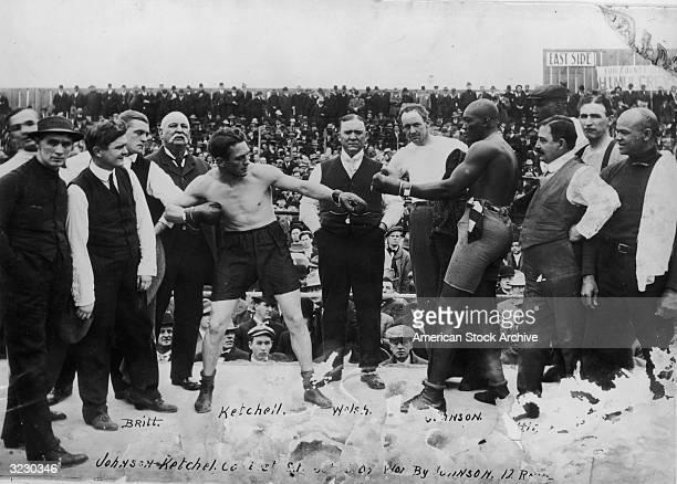 American boxers Stanley Ketchell and Jack Johnson touch gloves while squaring off in the boxing ring before their fight San Francisco California...