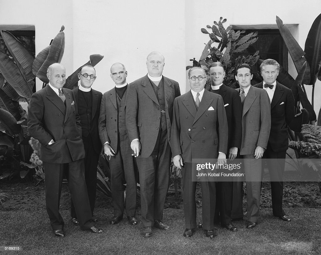 Hollywood producer Louis B. Mayer (1885 - 1957, 4th from right) with Cecil B. DeMille (1881 - 1959, left) and Fred Niblo (1874 - 1948, right). All three men are founders are AMPAS (the Academy of Motion Picture Arts and Sciences), and are accompanied by a number of clerics wearing dog collars.