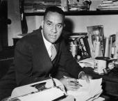 American author Richard Wright sits at a desk with a pen in his hand shortly before the publication of his book 'White Man Listen' Paris