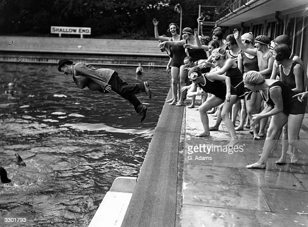 A group of bathing girls at Chiswick open air baths throw their fullyclothed friend into the shallow end