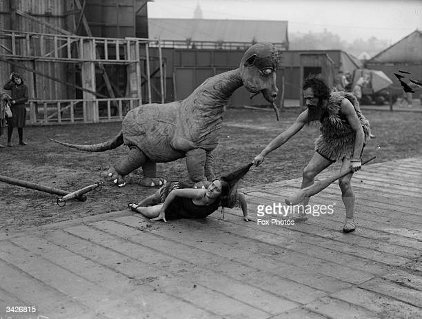 A prehistoric caveman rescues his wife from the attentions of a dinosaur during the Railway centenary and pageant celebrations at Liverpool