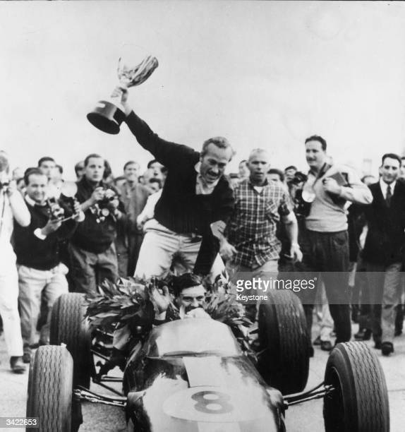 Scottish racing driver Jim Clark carries Lotus boss Colin Chapman holding the trophy aloft on the back of his Lotus car after winning the 1963...